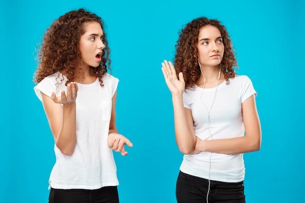 Женщина обижается на сестру-близнеца в наушниках над синим.