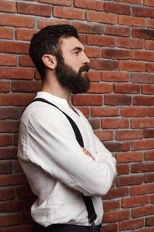 Молодой красавец позирует со скрещенными руками на кирпичной стене.