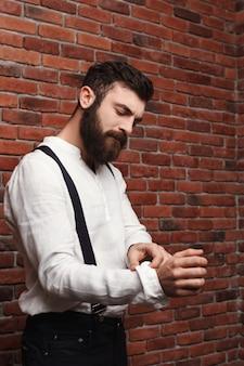 レンガの壁にシャツを修正する若いハンサムな男。