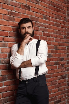 Представлять молодого красивого человека думая на кирпичной стене.