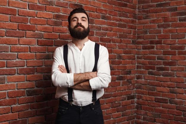 レンガの壁に組んだ腕でポーズをとって若いハンサムな男。