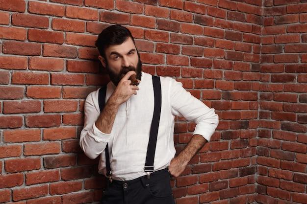Сигары зверского молодого красивого человека куря на кирпичной стене.