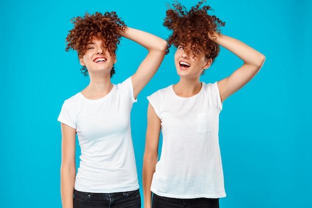 Две женщины-близнецы, держа волосы, шутки над синим.
