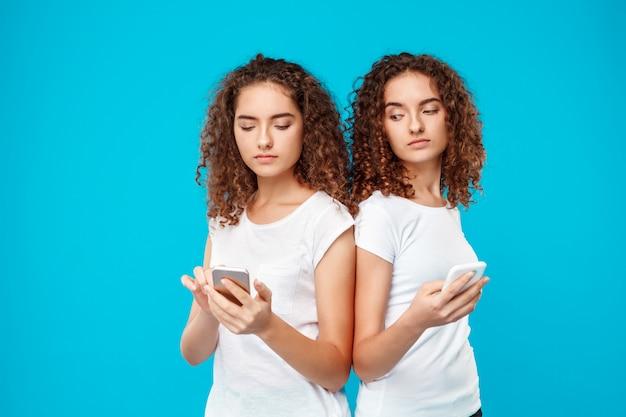 Две женщины-близнецы глядя на телефоны над синим.