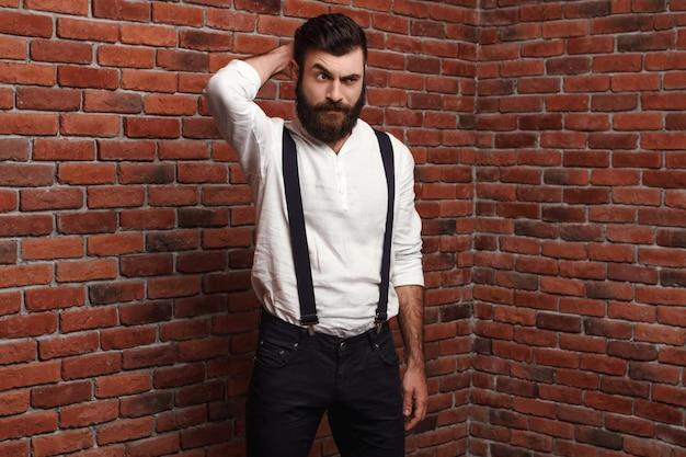 レンガの壁でポーズをとって若いハンサムな男。