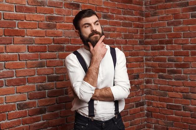 レンガの壁でポーズを考えて若いハンサムな男。