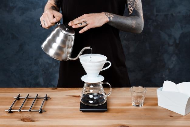 男性のバリスタがコーヒーを淹れています。別の方法を注ぎます。