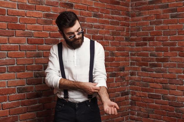 Молодой красавец, исправляя рубашку на кирпичной стене.