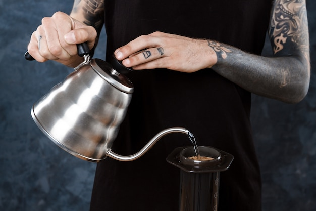 男性のバリスタがコーヒーを淹れています。エアロプレスの代替方法。