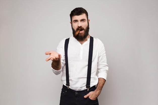 若いハンサムな男が白でポーズします。