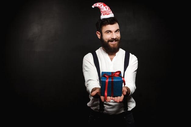 黒の上にクリスマスギフトボックスを置く若いハンサムな男。