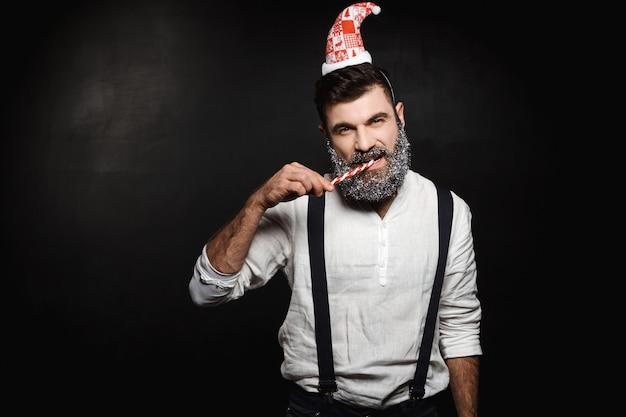 黒の上にクリスマスのお菓子を食べる若いハンサムな男。
