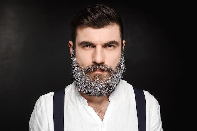 Портрет молодого красивого человека с бородой в снеге над чернотой.
