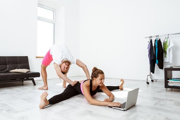 Молодые красивые спортивные пары обучения йоги асаны дома.
