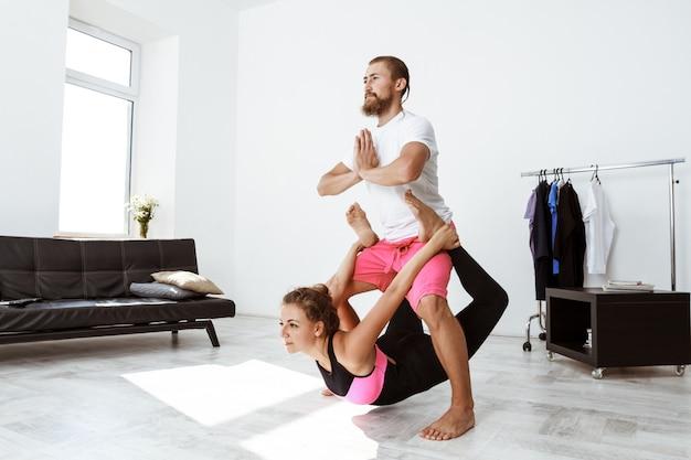 Асаны йоги партнера молодых красивых спортивных пар практикуя дома.