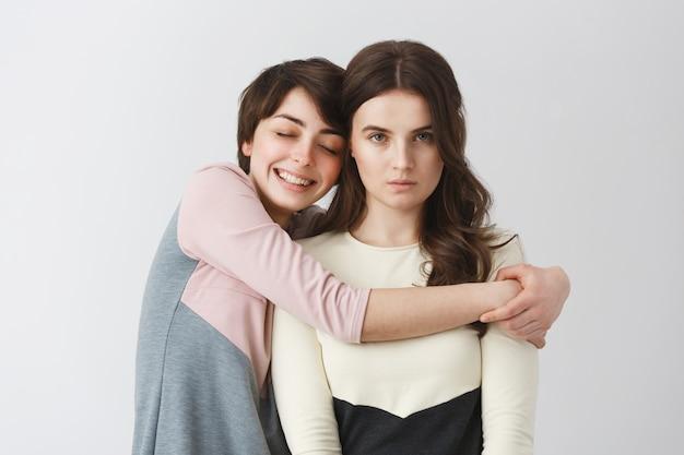 大学パーティーでの写真のための不機嫌そうなガールフレンドを抱き締める短い髪の幸せなレズビアンの女の子の肖像画。愛との関係。