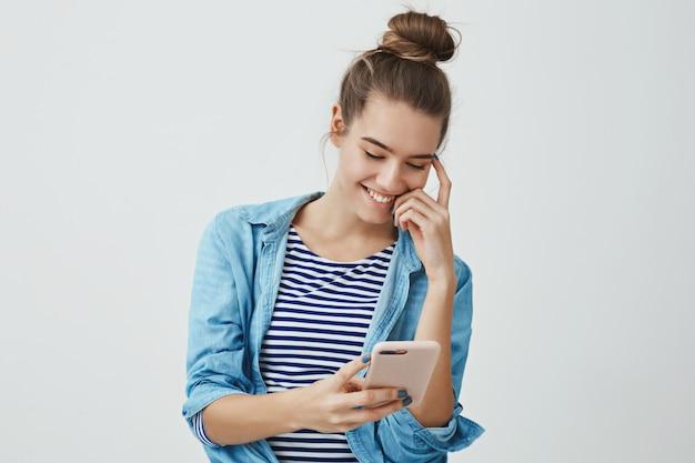 Беззаботная привлекательная молодая европейская женщина, улыбаясь счастливо держа смартфон, глядя на дисплей