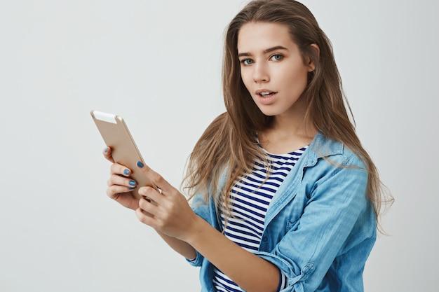 Привлекательная современная тысячелетняя молодая модная нахальная женщина держит цифровую таблетку