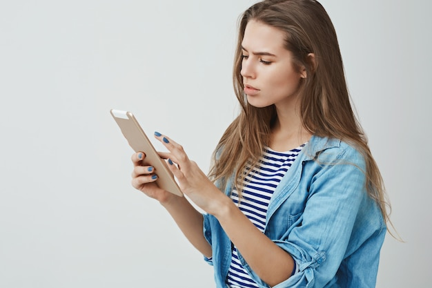 Выглядящая серьезно занятая привлекательная молодая успешная женщина используя цифровую таблетку