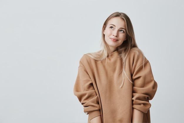 ブロンドの髪を染めた喜んで笑顔の女性、夢のような表情、孤立した居心地の良いセーターを着ています。魅力的な肯定的な女性は夢のように上向きに見える