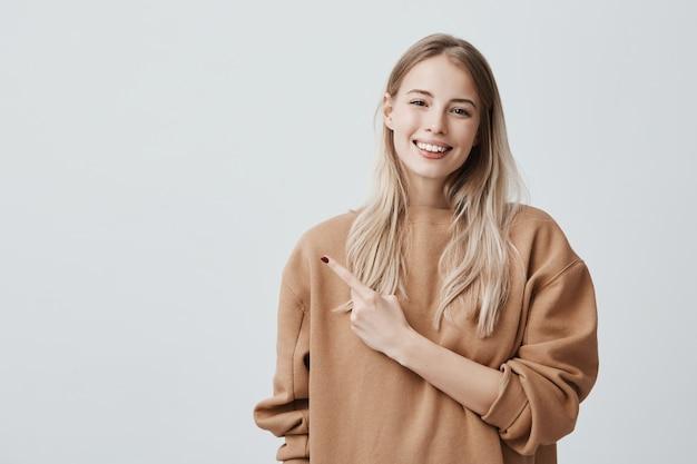 陽気で幸せな顔の表情で、人差し指で人差し指を指して満足そうな表情をしている魅力的な見栄えの良い笑顔の若い女性。