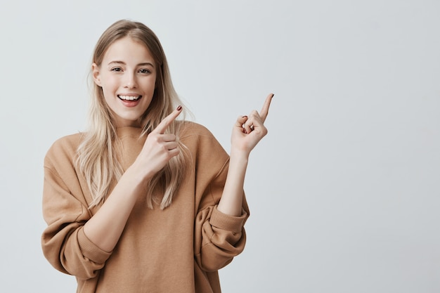 かわいい陽気な金髪の若い女性が広く笑みを浮かべて指を離れて指して、面白いと刺激的な何かを示す