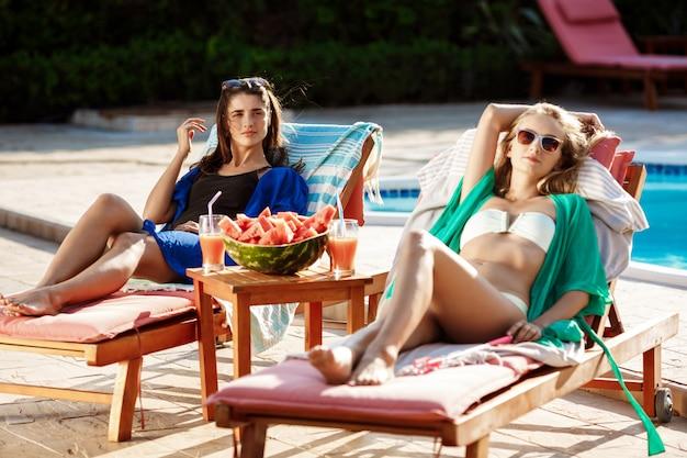日光浴、リラックス、スイミングプールのそばの長椅子で休んで美しい女性