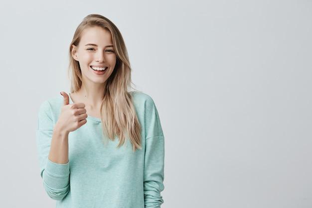 Счастливая молодая кавказская женщина нося голубую рубашку с длинными рукавами делая большой палец руки вверх по знаку