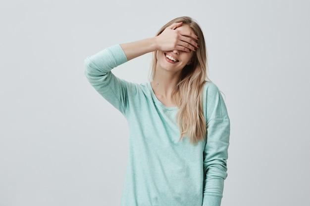 Портрет молодой девушки модели, скрывая глаза за ладони и широко улыбаясь, чувствуя радость.