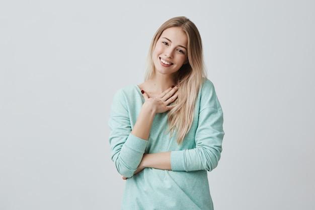 Счастливая блондинка, рада получить подарок от мужа, имеет радостное выражение, широко улыбается с зубами. красивая довольная женская модель в голубом свитере, выражающая положительные эмоции
