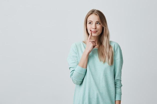カジュアルな服装で長いブロンドの髪を持つ白人女性モデルは夢のような表情で脇を探します
