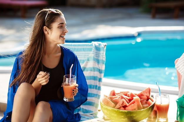 Красивая брюнетка женщина улыбается, пьет коктейль, сидя у бассейна