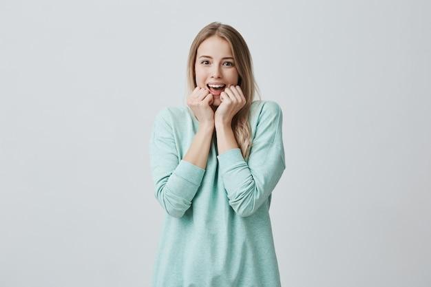 長いブロンドの髪を持つ驚いた若いきれいな女性は、口を開けて見え、気楽な何かを見て興奮し、カジュアルに着替えています。驚きと表情