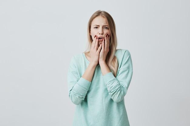 彼女が聞いたニュースにショックを受け、口を開いて頬に手を繋いでいるショックを受けて気絶した金髪のヨーロッパ人女性。おびえた恐怖の美しい女性モデル。否定的な感情