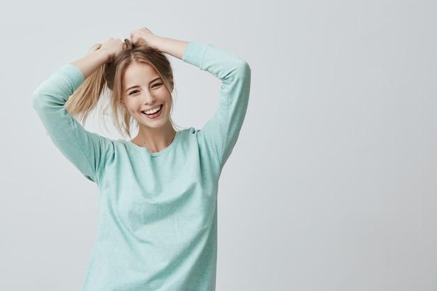 人間の顔の表情と感情。カジュアルな服を着てポニーテールで染めたブロンドのストレートの髪を持つ肯定的な若い美しい女性