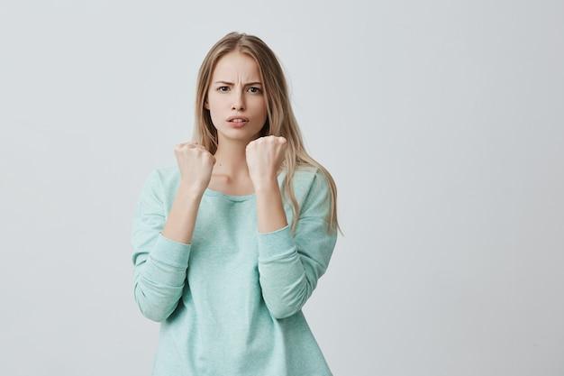 防御と保護。ブロンドの髪のカジュアルな服を着ている強いスポーツ女性と彼女の前で拳を握りしめている深刻な自信を持った表情は、攻撃と悪い扱いから身を守る