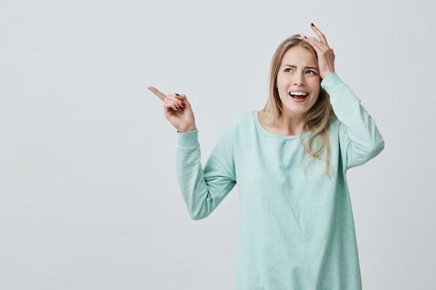 Красивая женщина с длинными светлыми волосами держит руку на голове, как будто она забыла что-то важное, указывая указательным пальцем в сторону