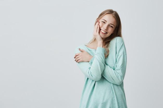 Довольная кавказская женщина с длинными белокурыми волосами в голубом топе широко улыбается и держит руку на щеке