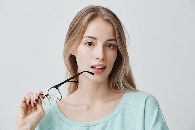 美しい金髪の思慮深い女性は、しんみりと眼鏡を外し、思考に深く入り、心の中で何かを分析し、