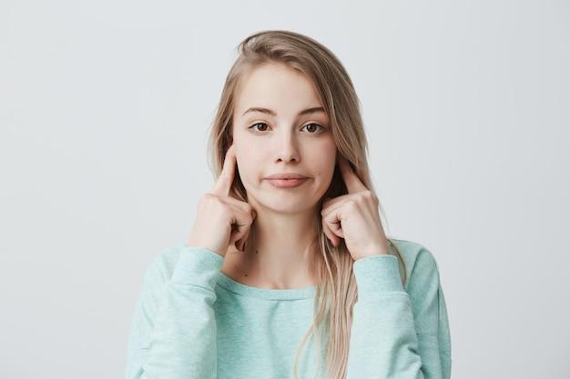 人間の否定的な感情、反応、態度。ブロンドの髪を染めた髪を耳で塞いでいるイライラしたイライラした女性は、騒々しい迷惑なノイズでイライラしていて、仕事に集中できません