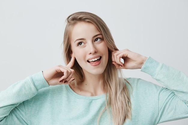 ボディランゲージ。神秘的な笑顔と遊び心のある表情で彼女の言われたことを聞かないふりをして、耳をふさいで、よそ見をして、カジュアルな服装の美しい若いブロンドのヨーロッパの女性