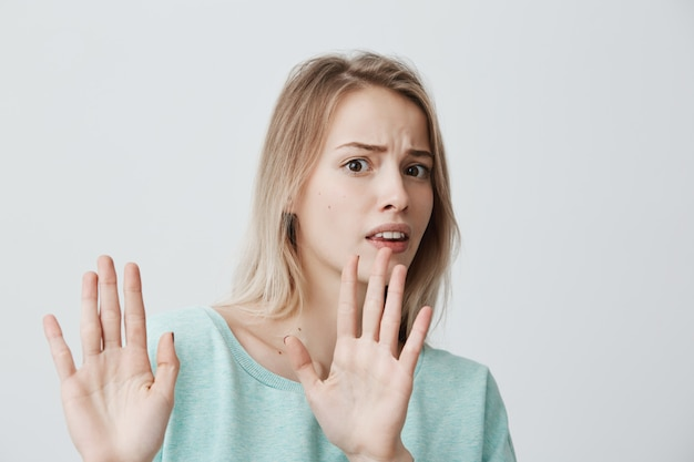 Раздраженная испуганная белокурая молодая самка с прямыми светлыми волосами в синем свитере позирует у стены, держа руки в жесте остановки, пытаясь защитить себя, говоря: «прекрати это. язык тела.