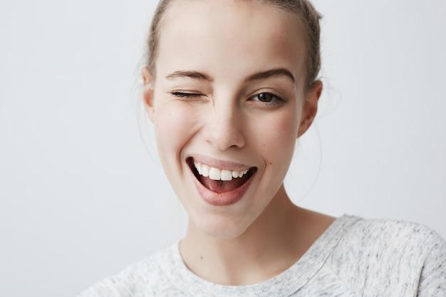 点滅してあなたといちゃつく美しい魅力的な若いブロンドの女性の肖像画。人間の顔の表情と感情