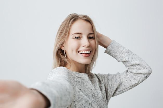 魅力的な暗い目をした金髪の女性は、カジュアルに服を着て広く笑って楽しい表情を持っています。ポーズしながら陽気な表情を持つ美しい女性