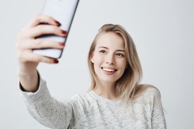 Красивая кавказская молодая женщина с длинными светлыми волосами и привлекательными темными глазами держит мобильный телефон, позирует для селфи