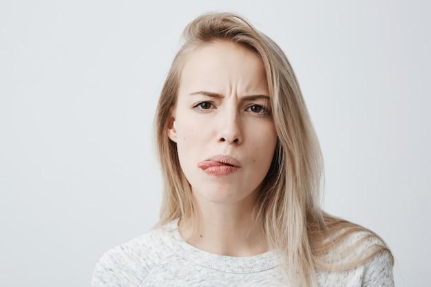 否定的な人間の反応、感情、態度。カジュアルな服装で顔をゆがめ、舌を突き出して、悪臭や悪臭のために吐き気を感じて、うんざりしてきしむ金髪女性のクローズアップの肖像画