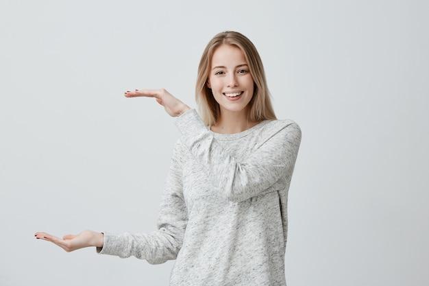 カジュアルな服装で染めた髪の女性との見栄えの良い美しいブロンドは、ボックスの長さの手で示しています。喜ばしい女性の笑顔は、大きなもののサイズを喜んで示しています。前向きな感情と感情