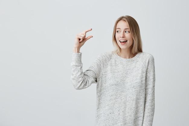Рад, что красивая блондинка в свободном свитере показывает что-то маленькое руками