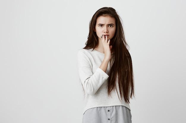 びっくりした表情のゆるいシャツを着たショックを受けた女性、予期しないニュースを見つけ、彼女が言われた言葉を信じることができない、それは本当に感情的な女性が興奮して手で口を閉じる