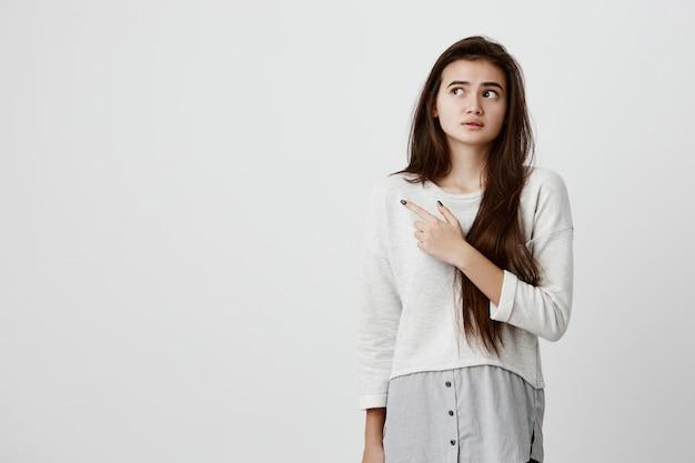 Удивленная потрясенная женская модель с прямыми темными волосами, одетая в повседневную одежду, смотрящая глазами с недоумением и недоумением, указывающая указательным пальцем на место для копирования